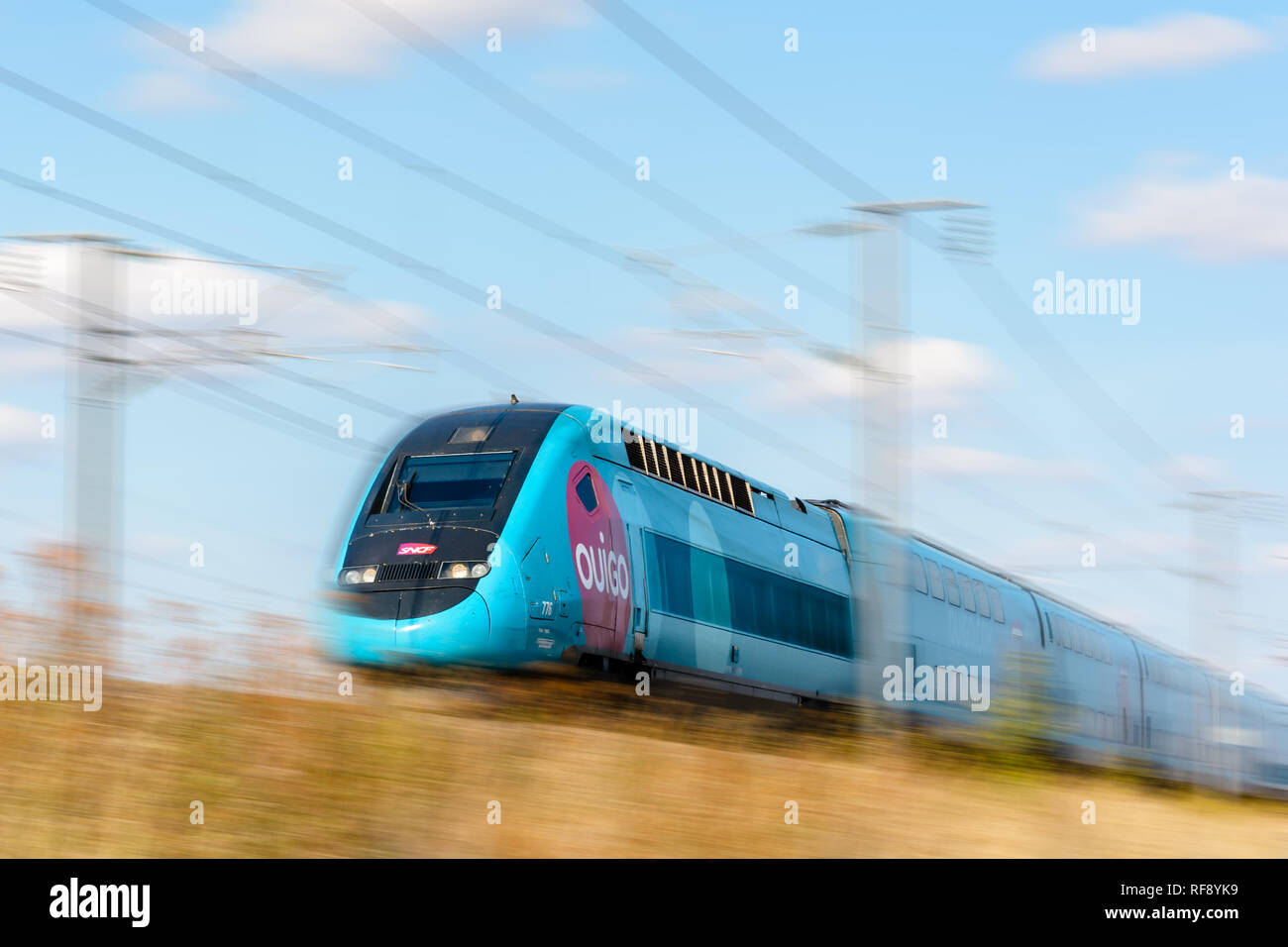A TGV Duplex high-speed train in Ouigo livery from french company SNCF driving at full speed on the East European high-speed line. - Stock Image
