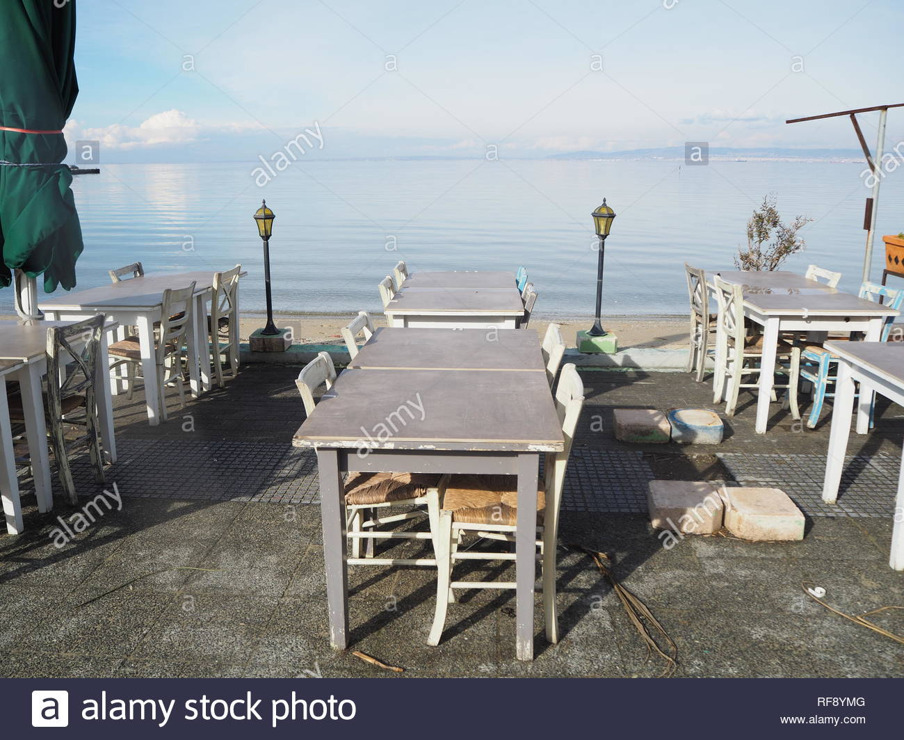 Unoccupied restaurant tables by the sea - Stock Image