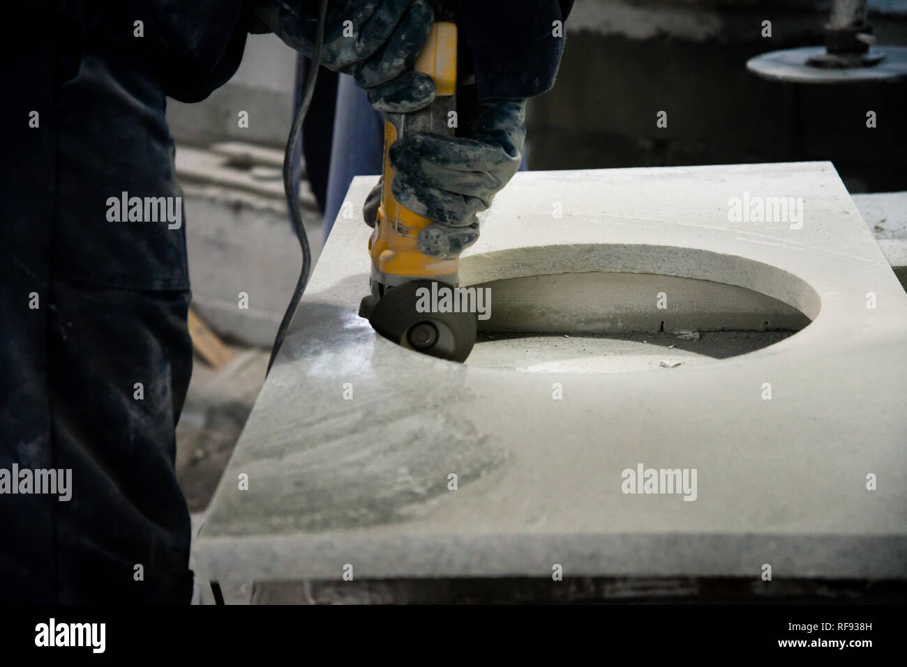 Man polishing marble stone table by small angle grinder. Stone cutter - Stock Image