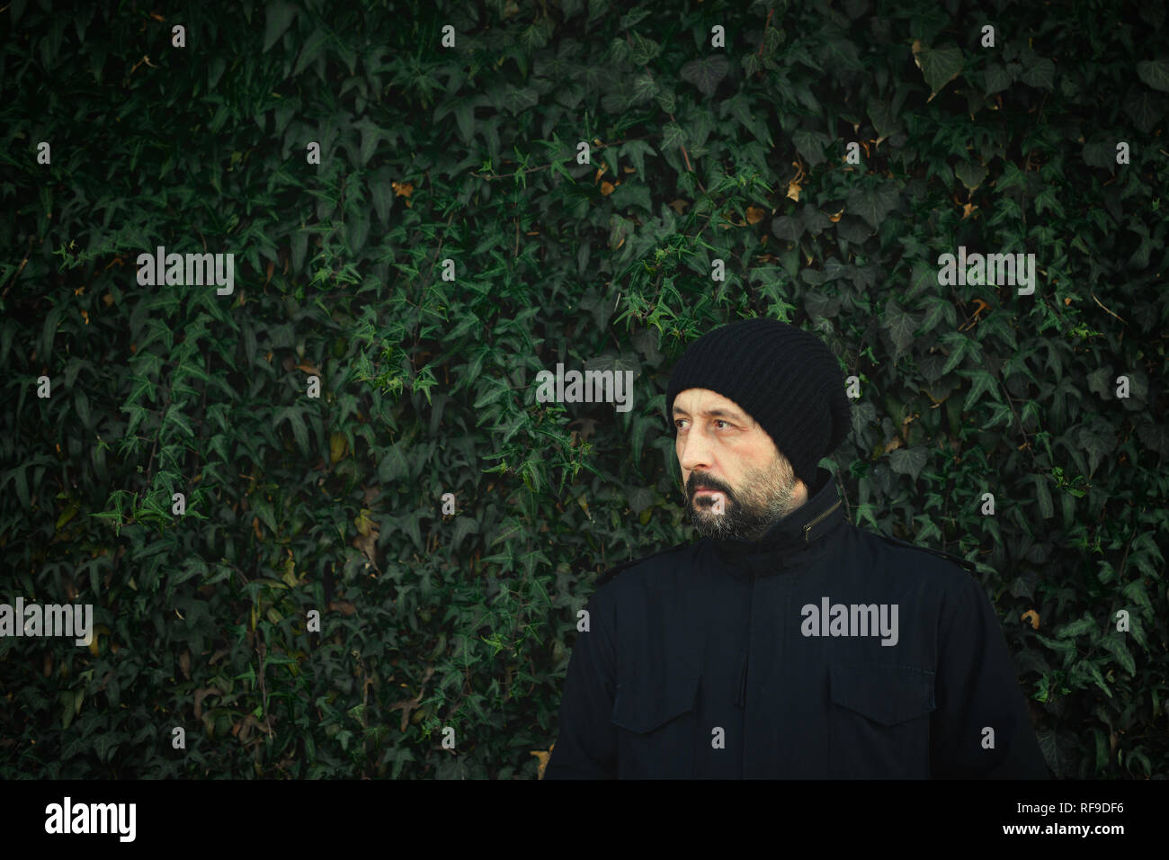 Portrait of cool handsome guy in military jacket standing outdoors against  the common ivy wall in 21c6e9c3ed30