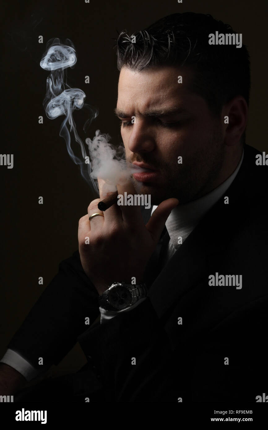 Low key portrait of adult smoker - Stock Image