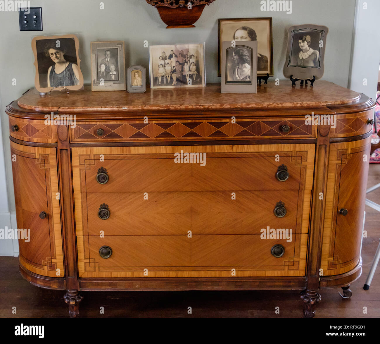 Antique light brown dining room sideboard with 3 large drawers,2 curved side doors & marble top. Monotone vintage family photos in frames on top. - Stock Image