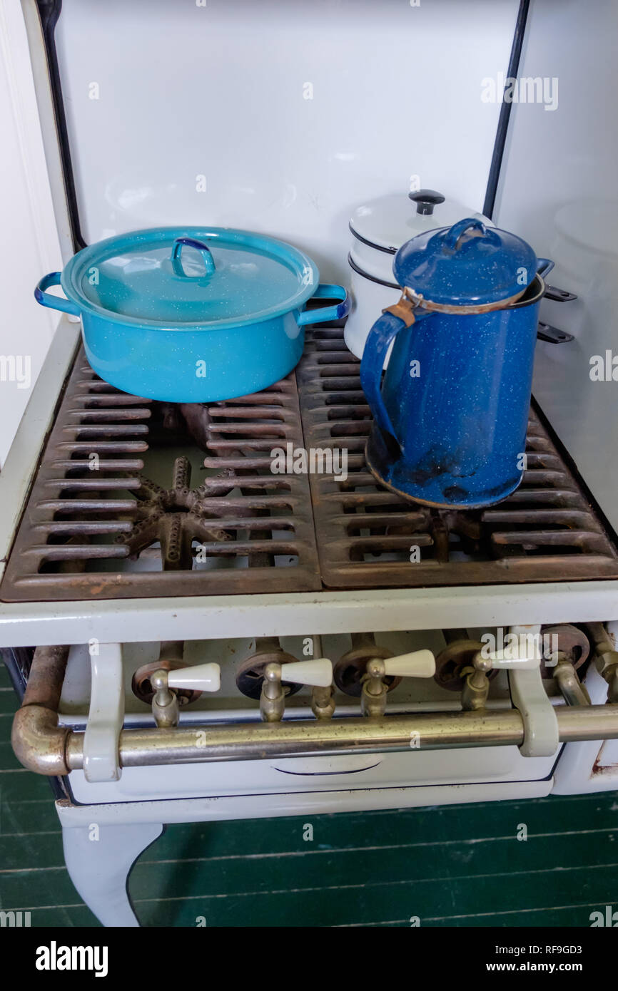 Antique Garland four burner gas stove with two blue and one white enamel vintage cookware. - Stock Image