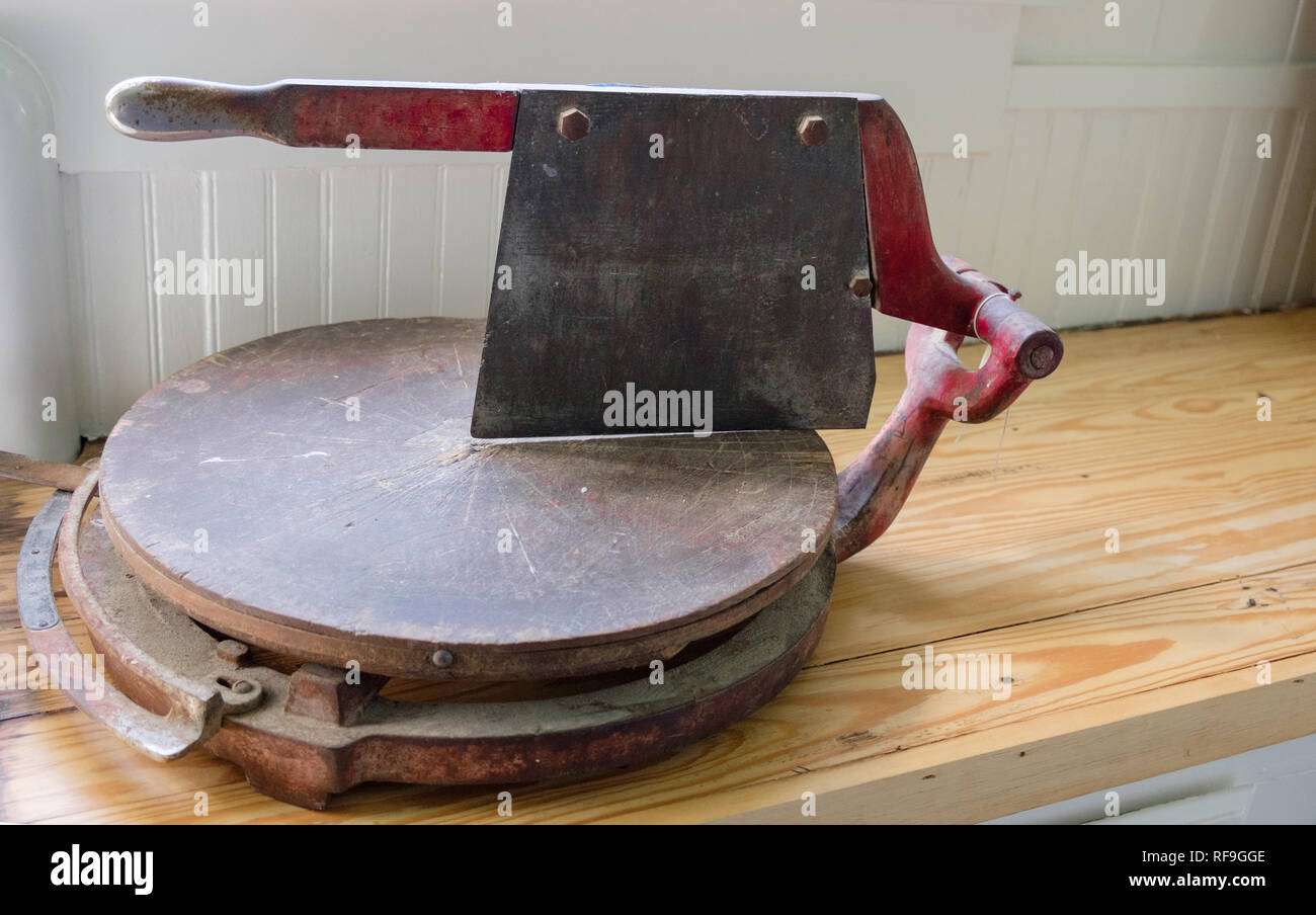 Vintage meat cleaver hinged to chopping board. - Stock Image