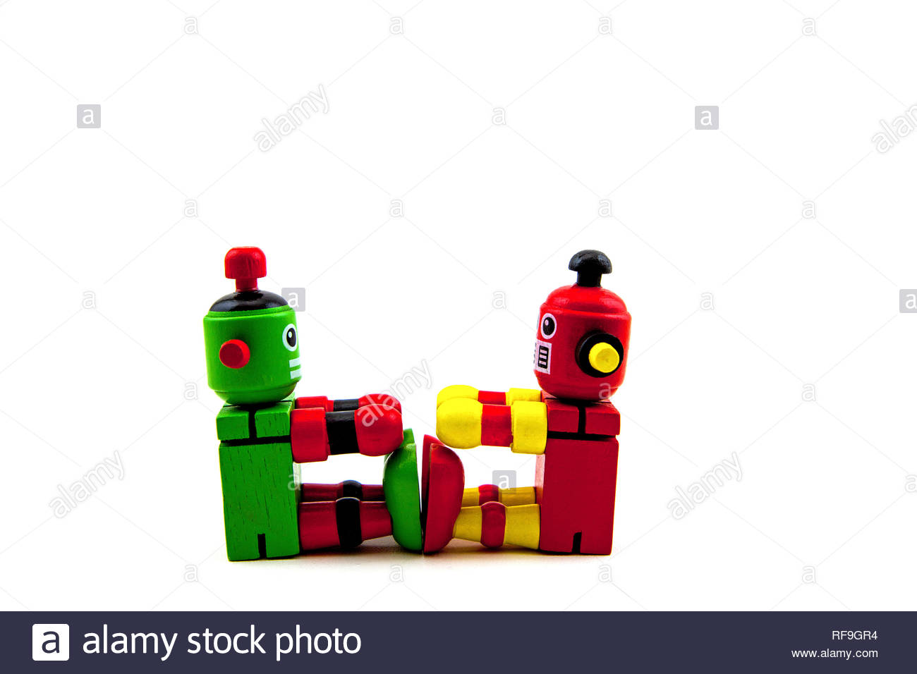 2 wooden toy robots, red/yellow & green/red, sitting facing each other with feet touching. Concepts exercising, communication. Copy space on white - Stock Image