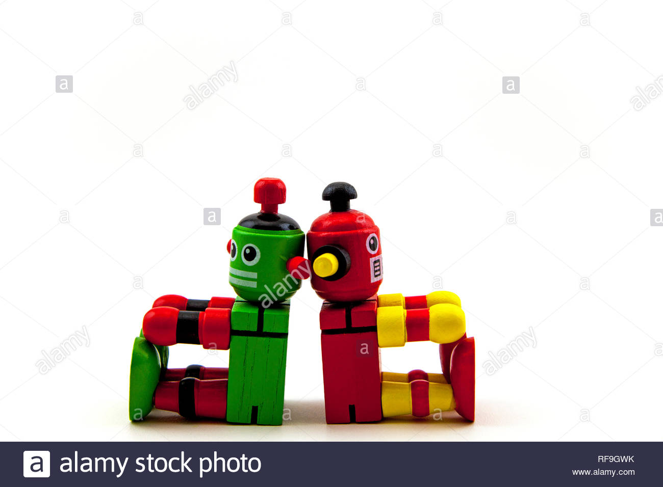 2 wooden toy robots, red / yellow & green / red, sitting back to back. Copy space on a white background. Concepts: no communication, argument, apart - Stock Image