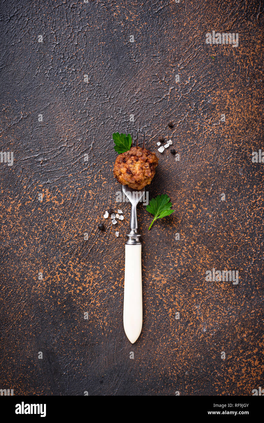 Homemade beef meatball on fork - Stock Image