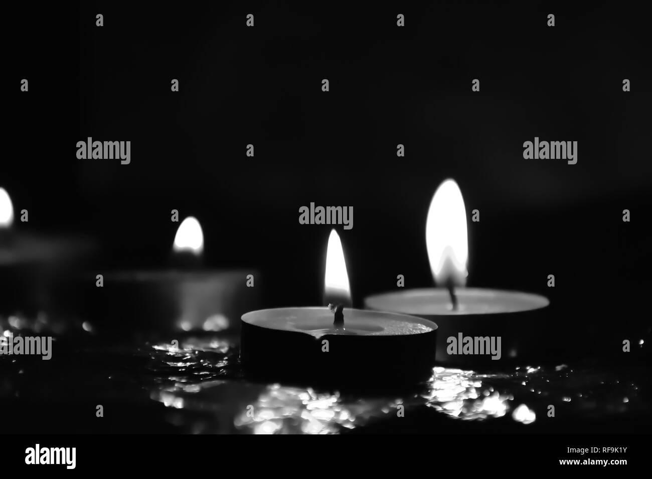 Beautiful Tea candle light glowing in darkness - Stock Image