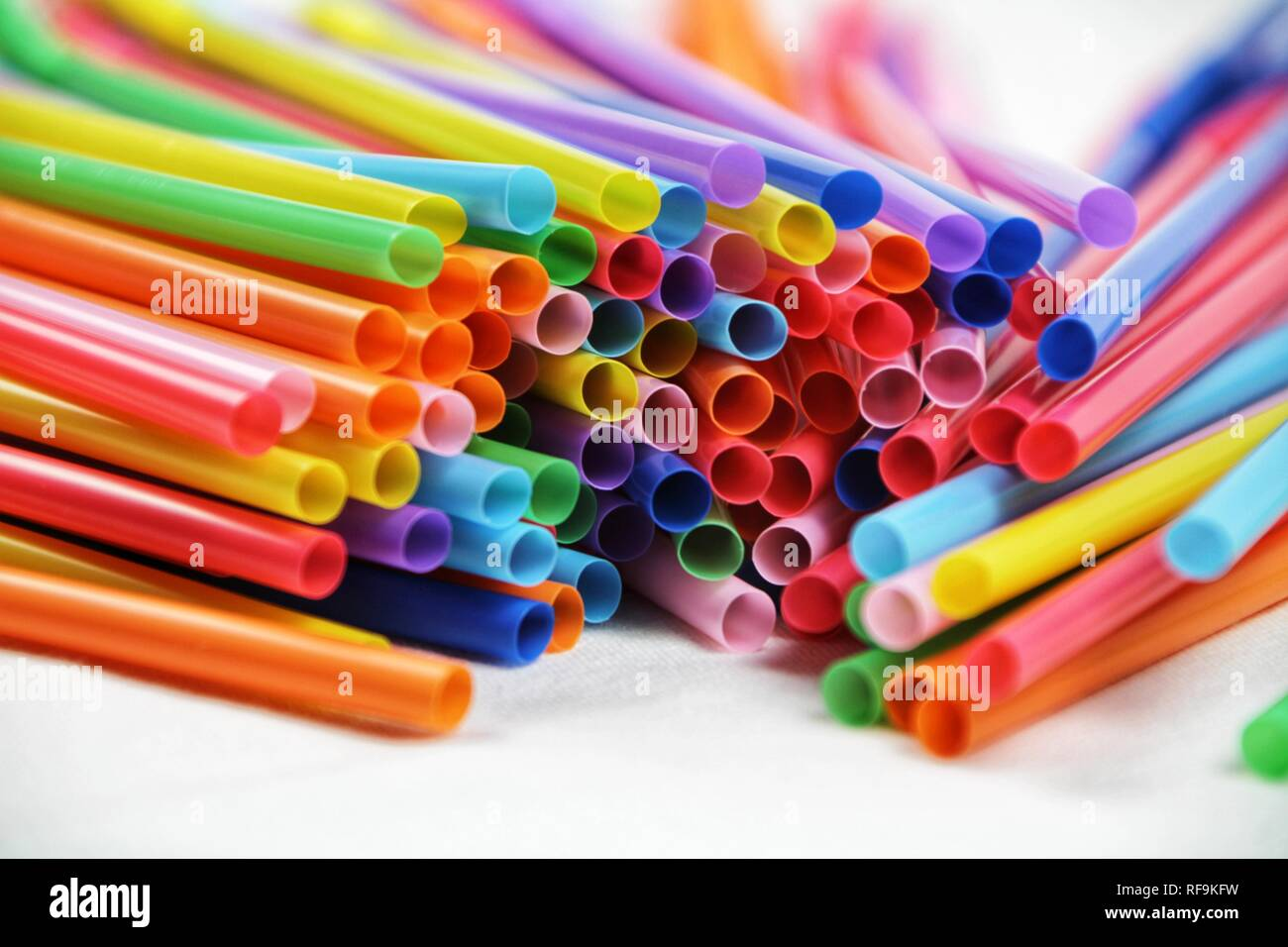 Colorful plastic drinking straws close up white background - Stock Image