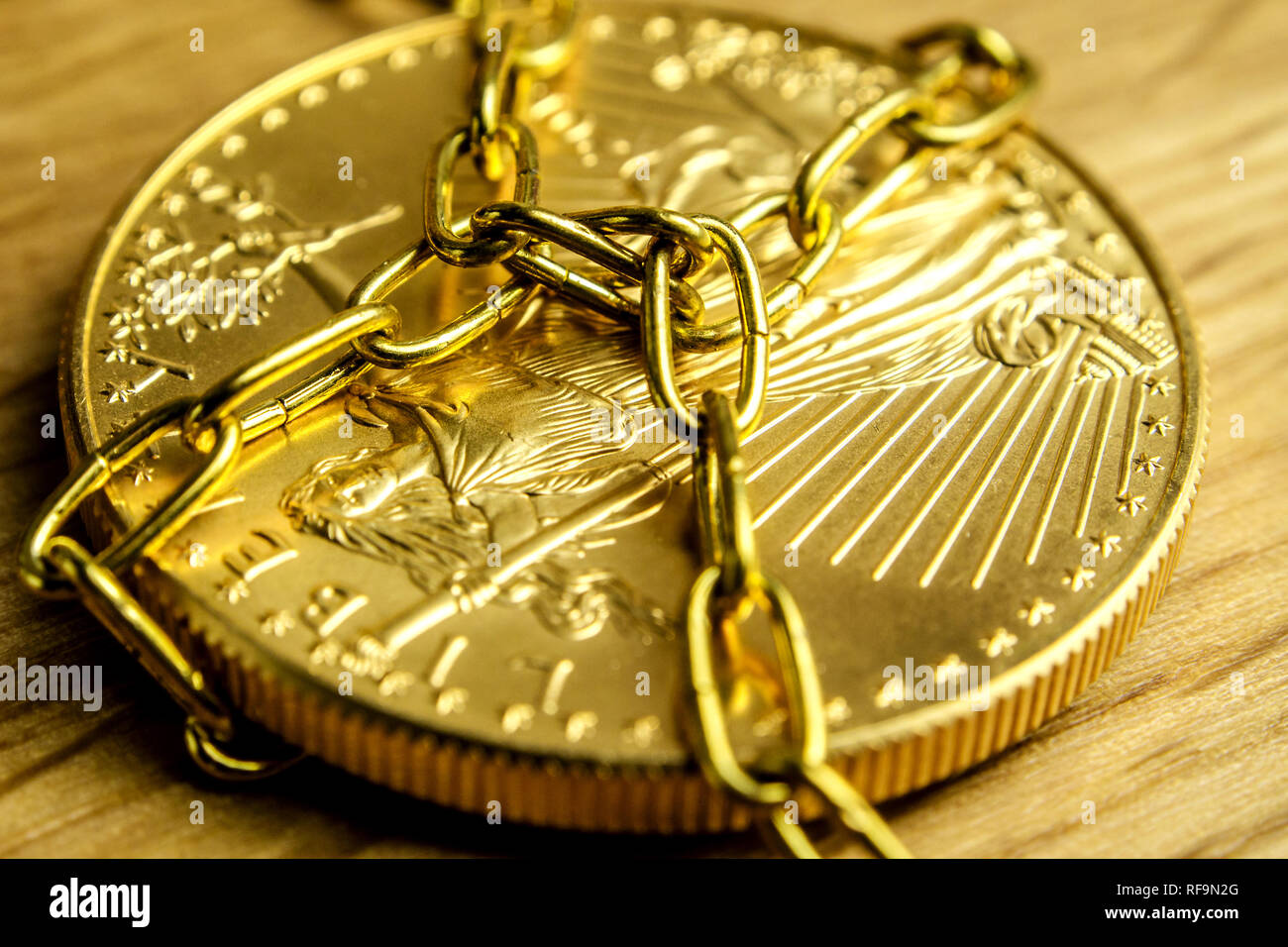 closeup of golden coin in golden chains laying on wooden background Stock Photo