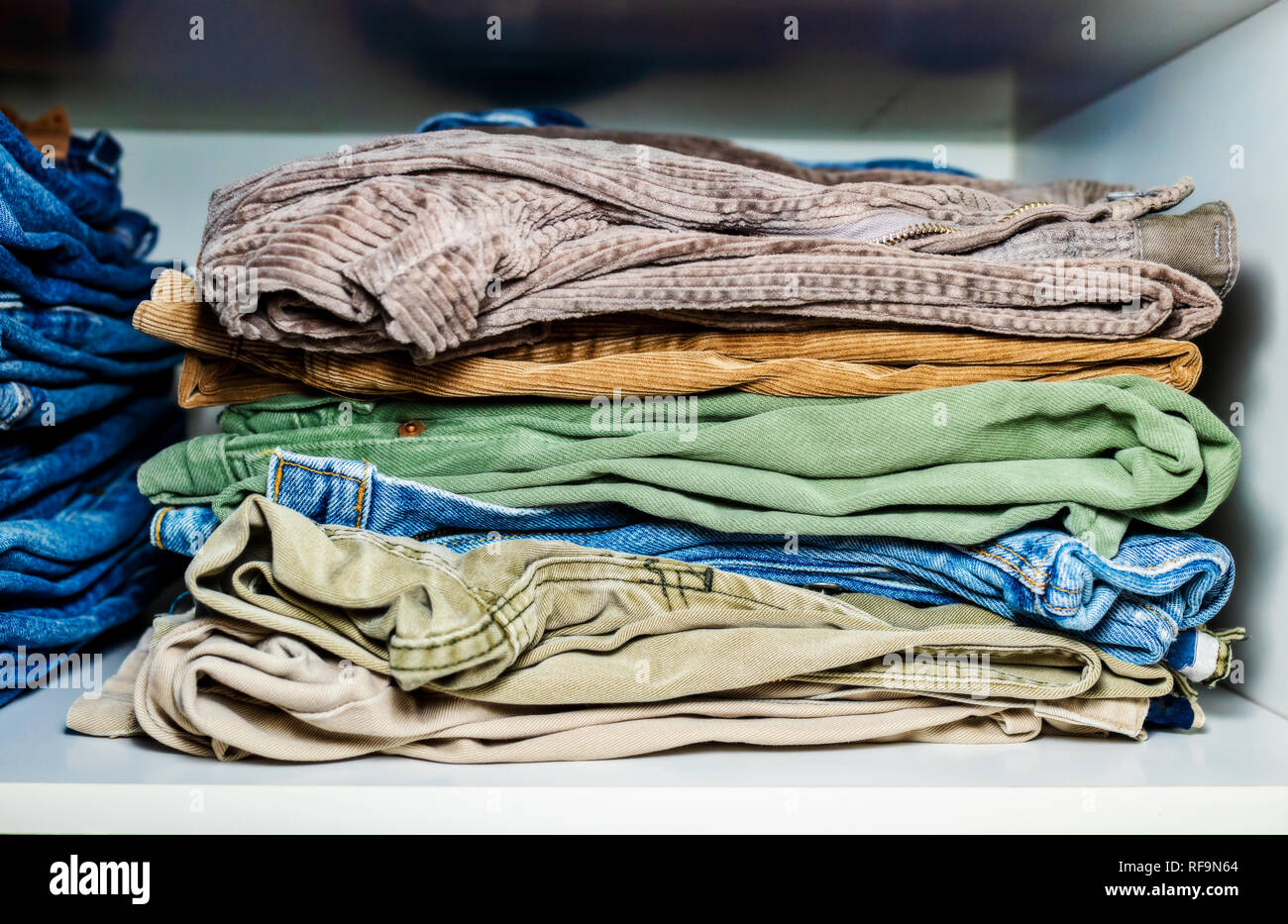 stack of mixed trousers in wardrobe - Stock Image