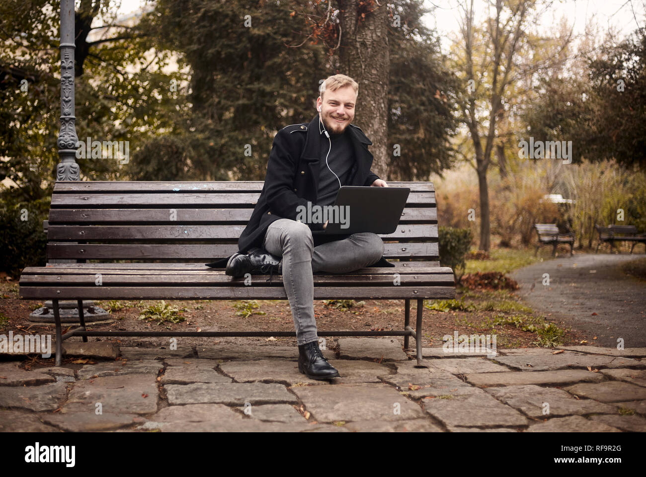 one young smiling and happy man, sitting on bench in public park,  using laptop, looking to camera. Formal wear or smart casual. Full length shot. - Stock Image