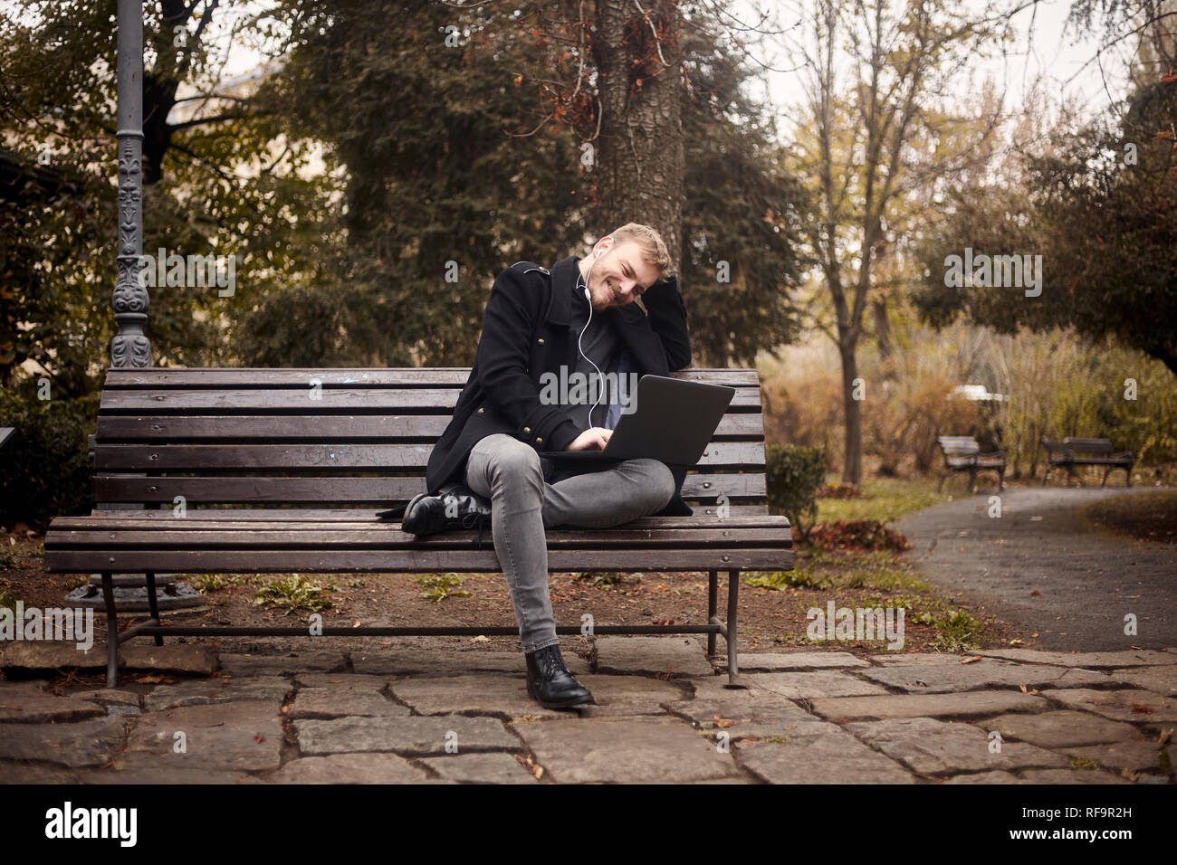 one young smiling and happy man, sitting on bench in public park,  using laptop, looking to computer. Formal wear or smart casual. Full length shot. - Stock Image
