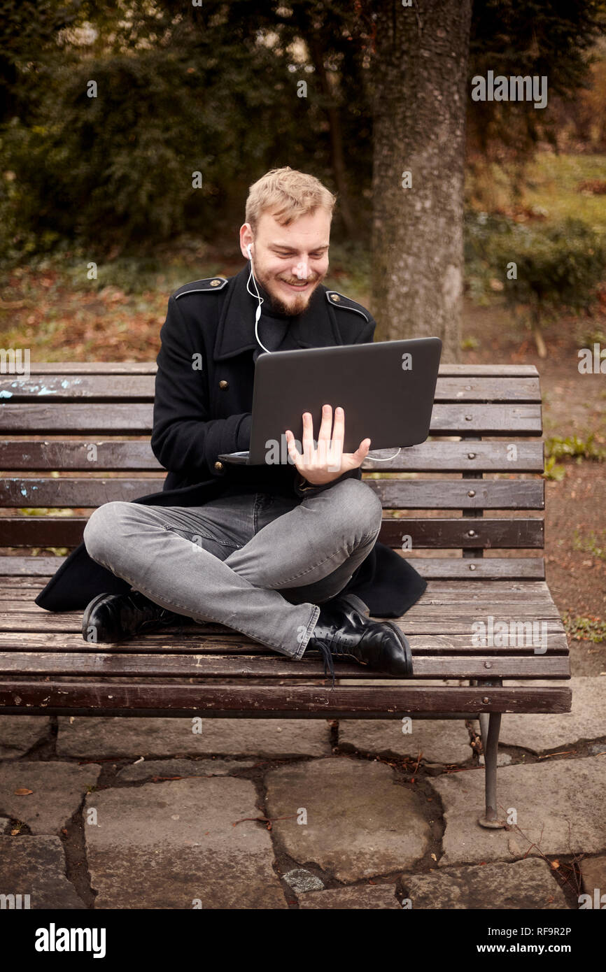 one young relaxed and smiling man, sitting casually on bench with crossed legs in public park, using laptop holding it with one hand. Formal wear or s - Stock Image