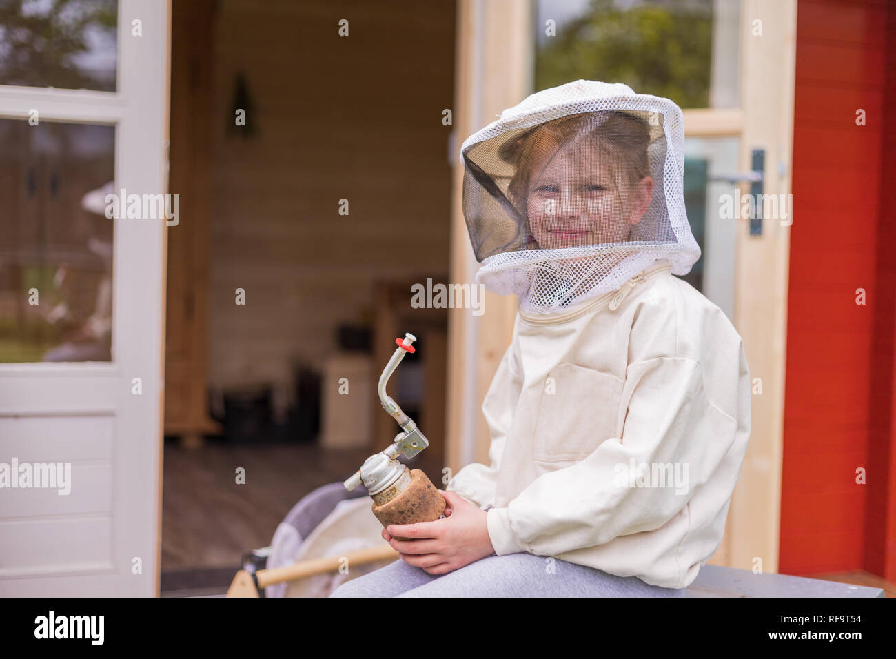 Portrait of a 7 year old girl with beekeeper suit for protection from the bees. In her hand she holds a beekeeper's pipe Stock Photo