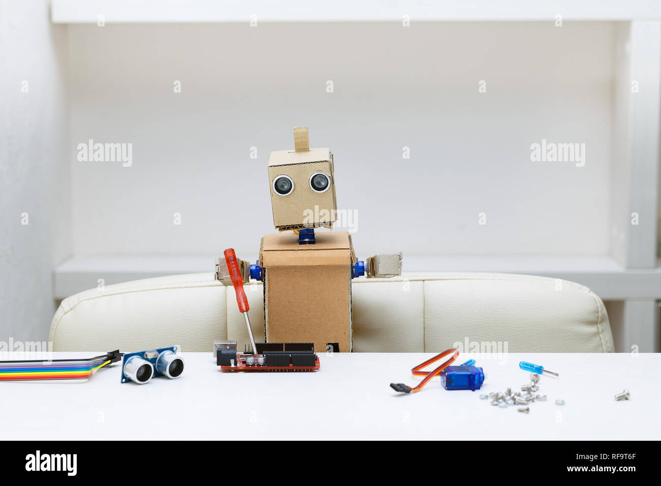 robot sits at a table and holds a screwdriver lying next to a robot