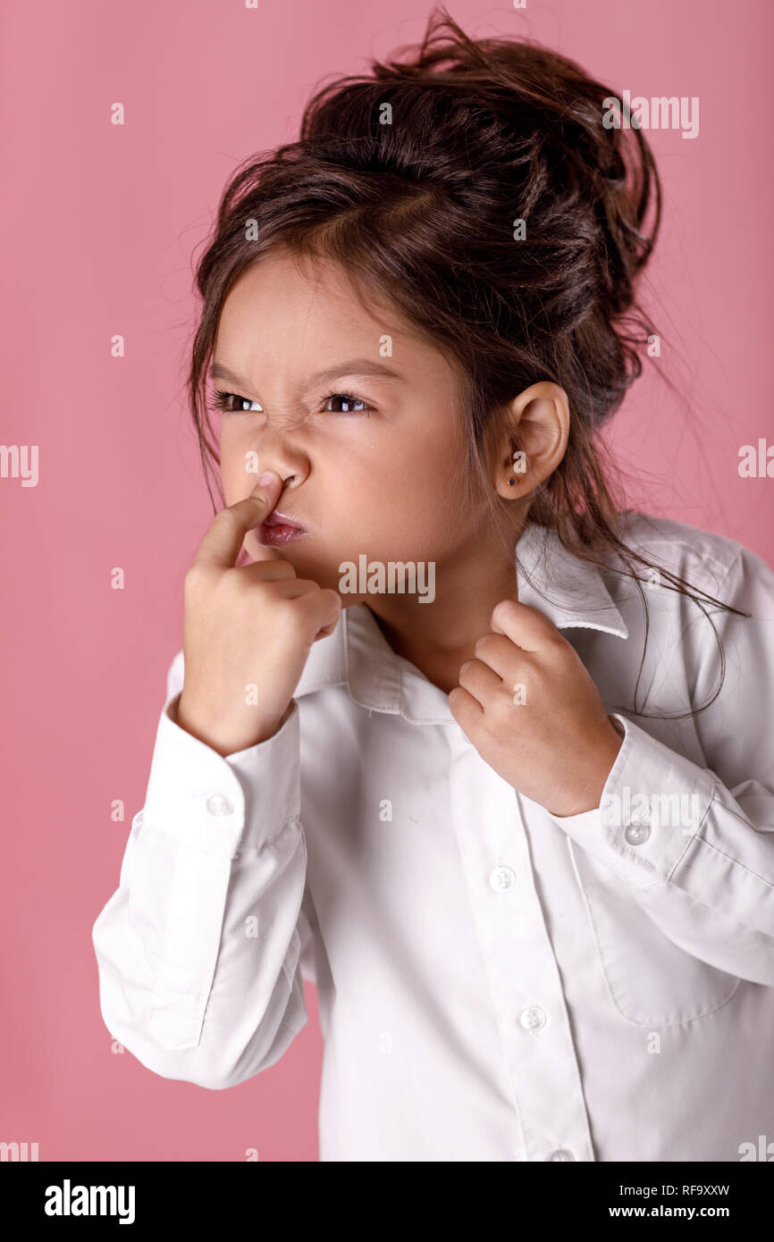 beautiful little girl in white shirt grimaces and fools - Stock Image