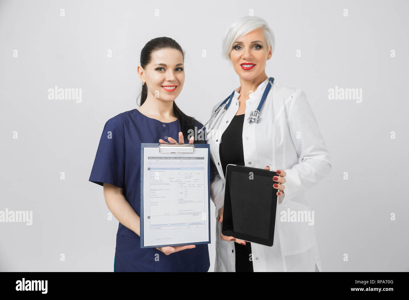 Two female doctors with tablet and sheet with analysis in hands isolated on white background - Stock Image