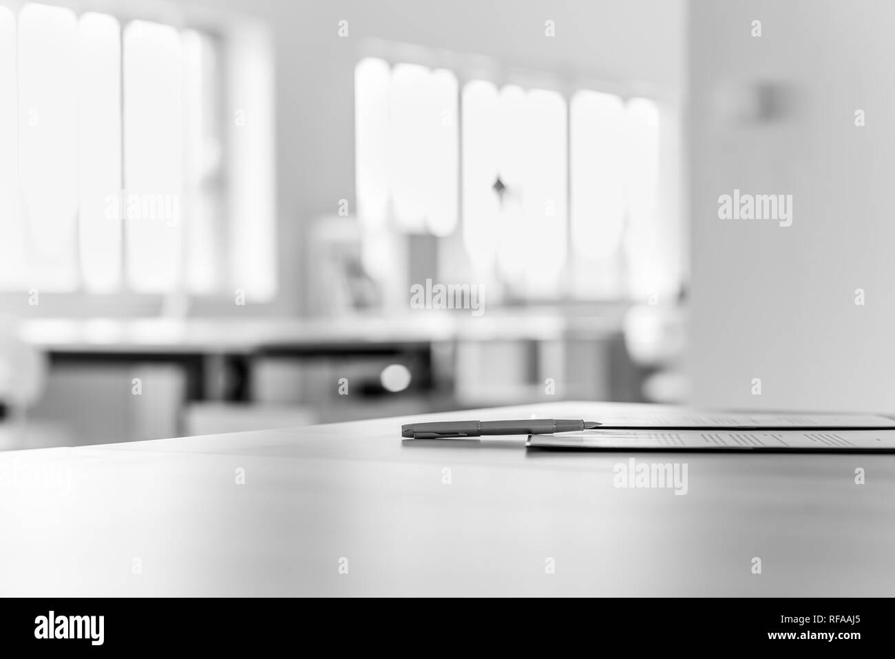 Monochrome image of application form and a pen lying on office desk. Stock Photo