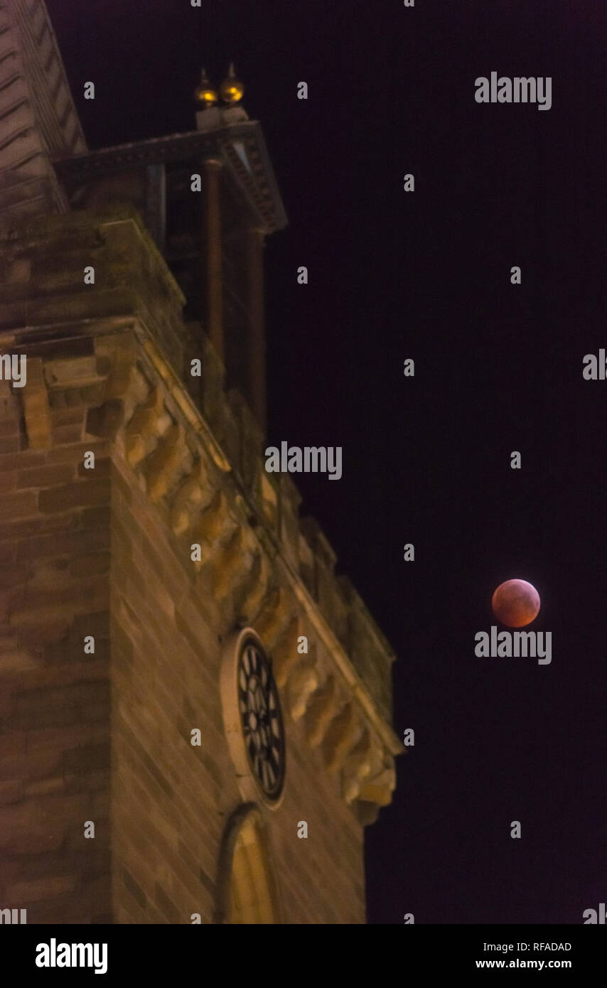 21st January 2019 supermoon. The blood moon of the total lunar eclipse illuminates the medieval clock tower of St John's Kirk in Perth city centre. Stock Photo