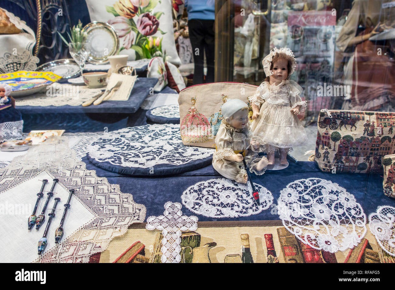White Belgian bobbin lace for sale as tourist souvenirs in shop window of gift shop / tourist store in the city Bruges, West Flanders, Belgium - Stock Image