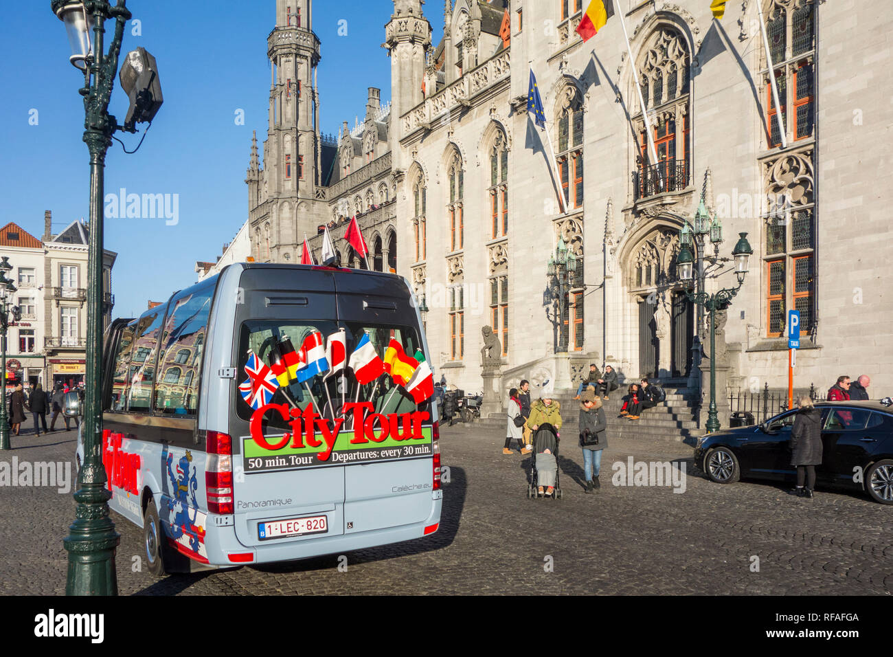 City Tour's minibus for guided sightseeing trip in front of the Provinciaal Hof / Province Court on the market place in Bruges, West Flanders, Belgium - Stock Image