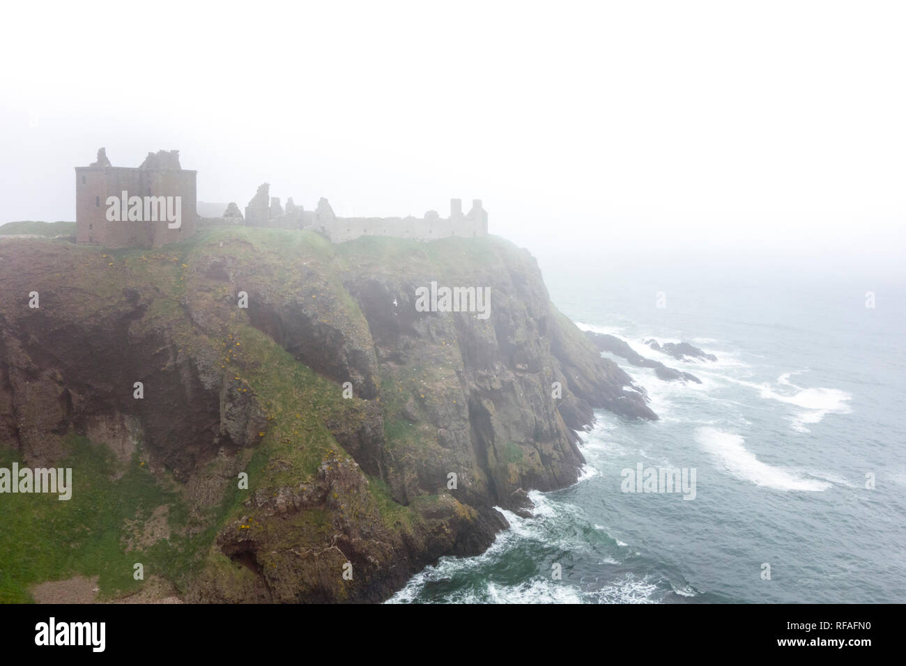 Dunnottar Castle in the mist, ruined medieval fortress near Stonehaven on sea cliff along the North Sea coast, Aberdeenshire, Scotland, UK - Stock Image
