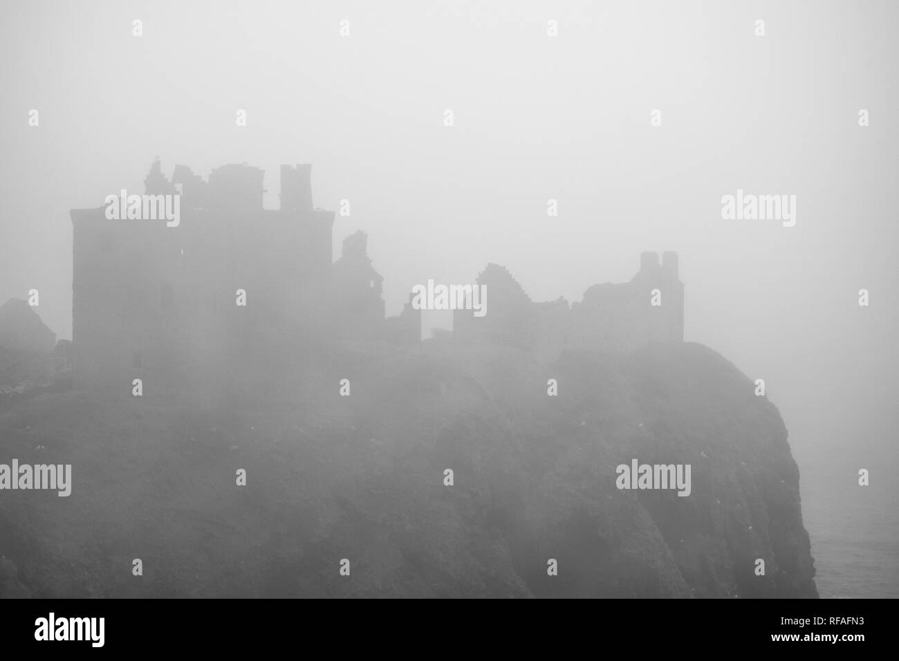 Dunnottar Castle in thick fog, ruined medieval fortress near Stonehaven on sea cliff along the North Sea coast, Aberdeenshire, Scotland, UK - Stock Image
