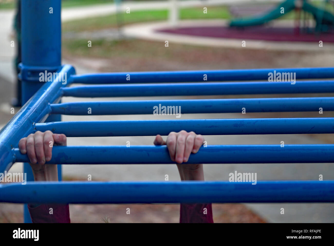 Children's hands gripping monkey bars while playing at the playground - Stock Image