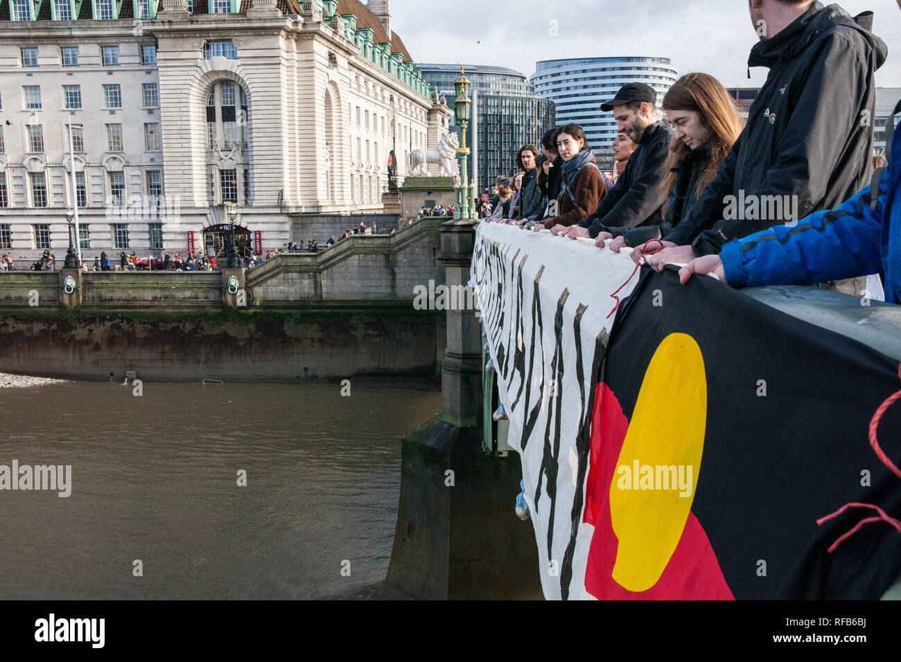 London, UK  25th January, 2019  Activists drop a banner and