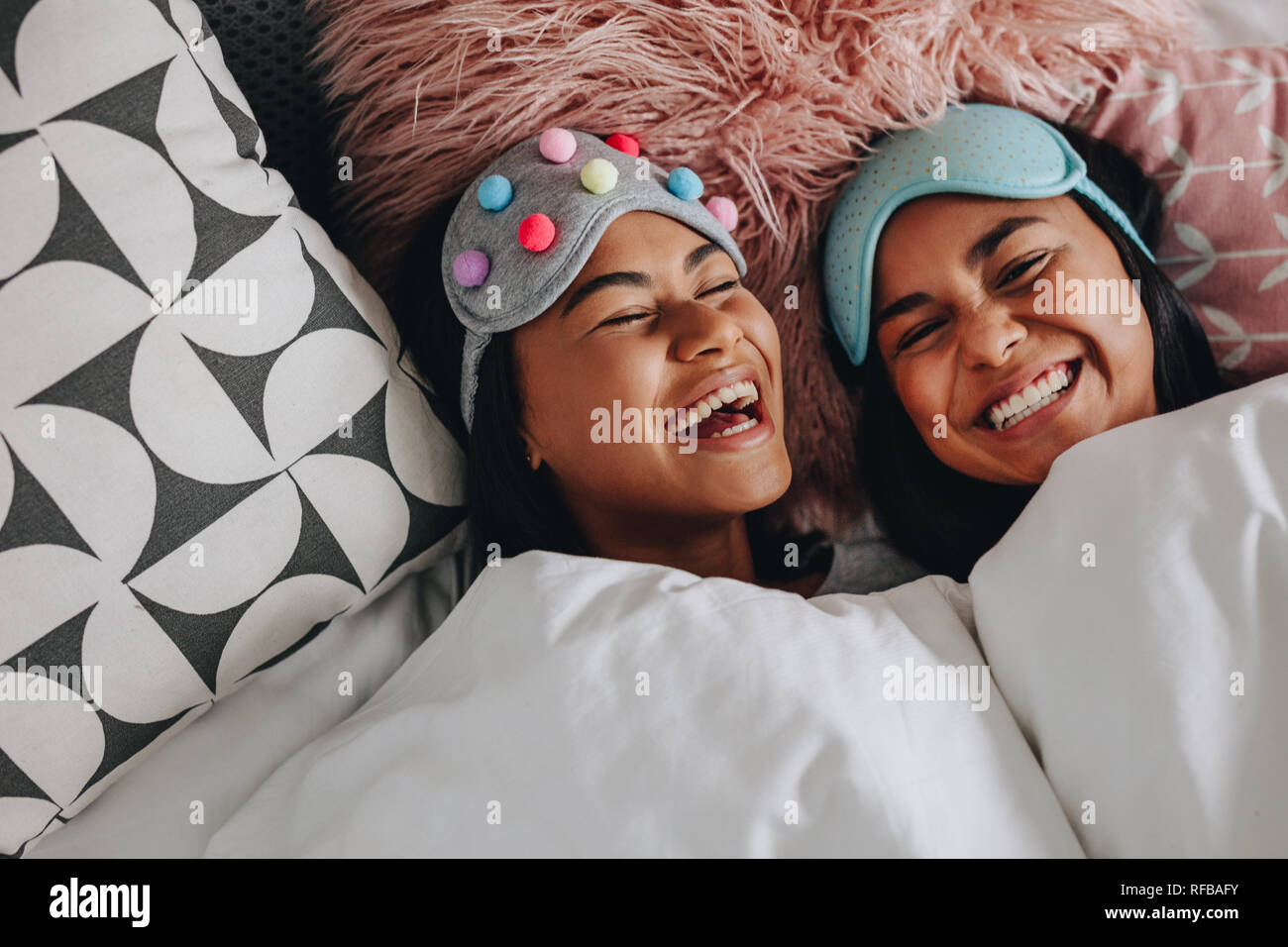 Top view of two girls laughing with eyes closed lying on bed having a sleepover. Girls with fancy sleep masks over the head laughing and having fun du - Stock Image