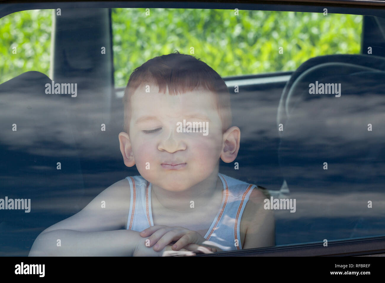 the boy pressed his nose to the glass in the car, during long trips, bored child - Stock Image