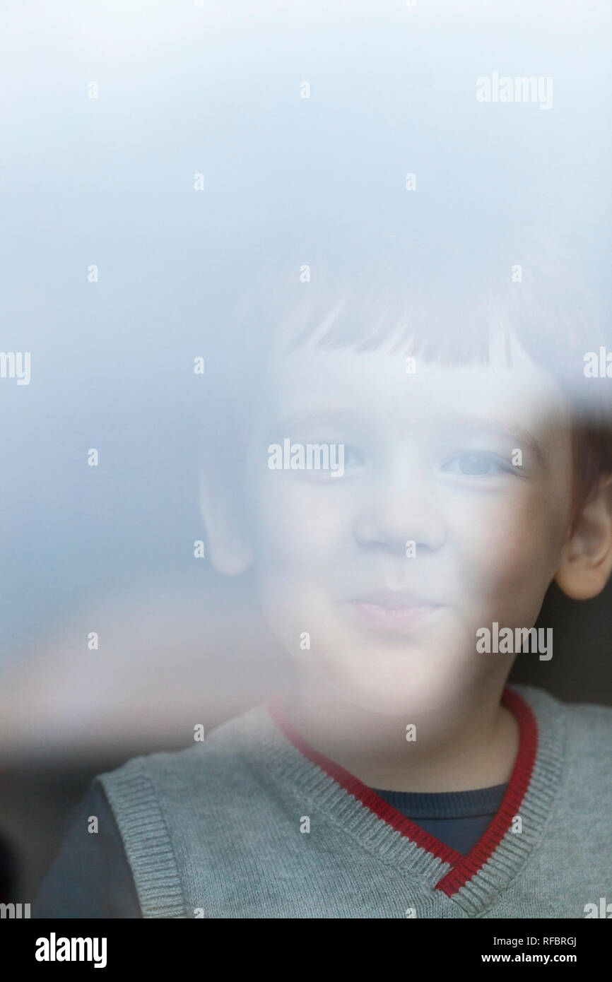 little boy is looking at the camera behind the glass of a building, seeing off an adult to work, a portrait of a boy with a smile - Stock Image