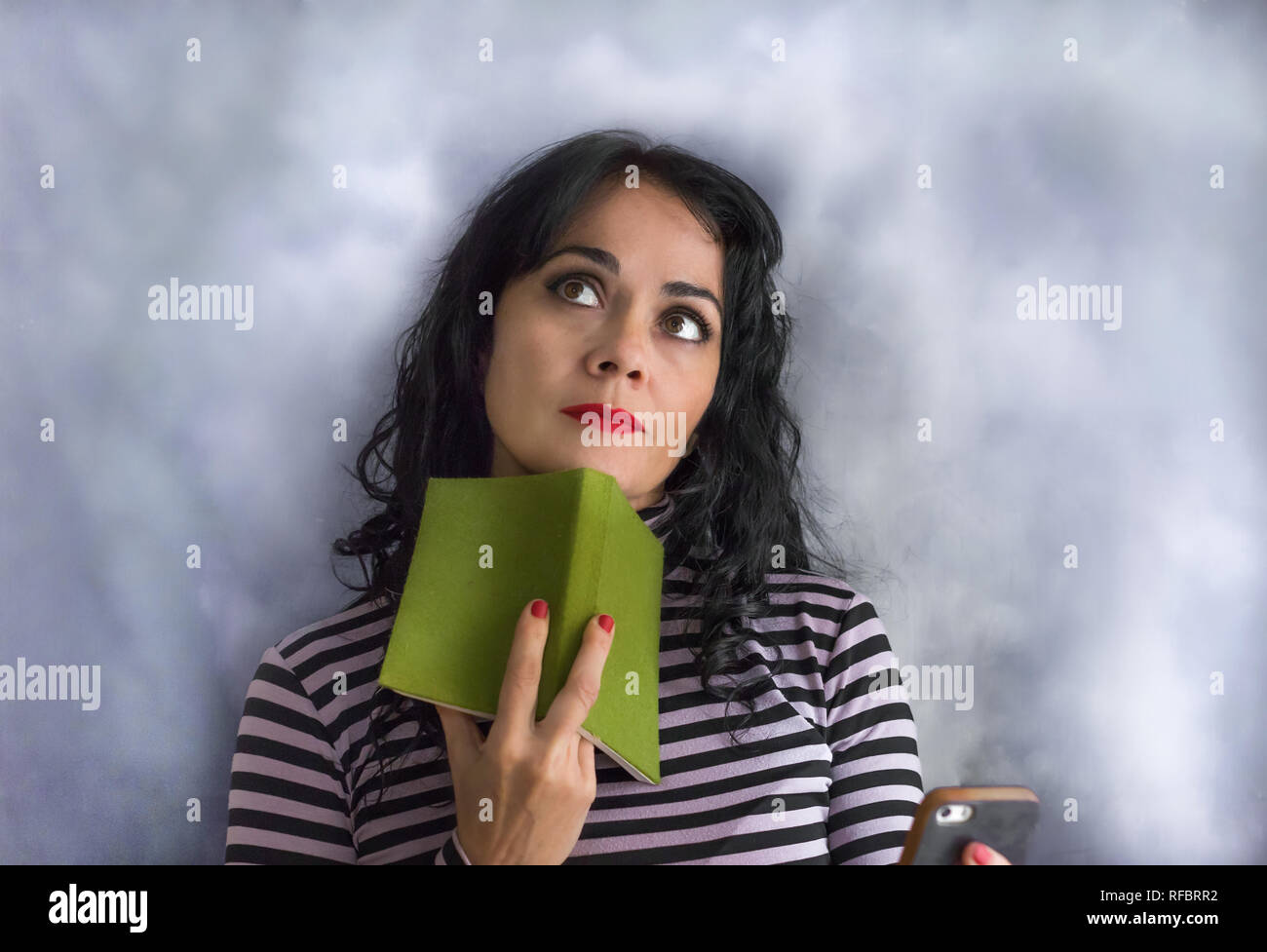 Young brunette woman with striped sweater with a book on her chin thinking about a question, isolated on a gray background - Stock Image