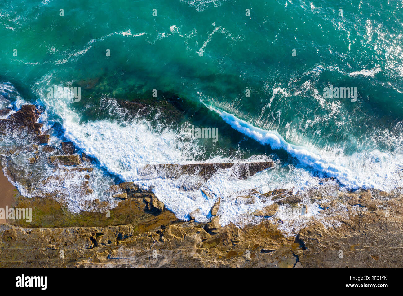 Top down view of the waves crashing onto the rock shelf at Dudley Beach - Newastle Australia. Aerial view of rugged coastal lanscape. Stock Photo