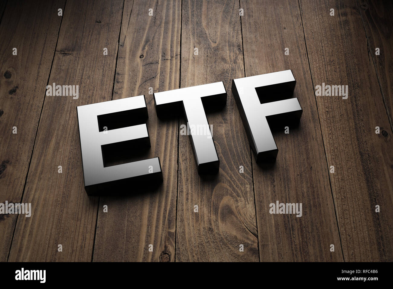 Metallic 3d ETF sign lying obliquely on wooden boards for an interesting header for Exchange Traded Funds with copy space Stock Photo