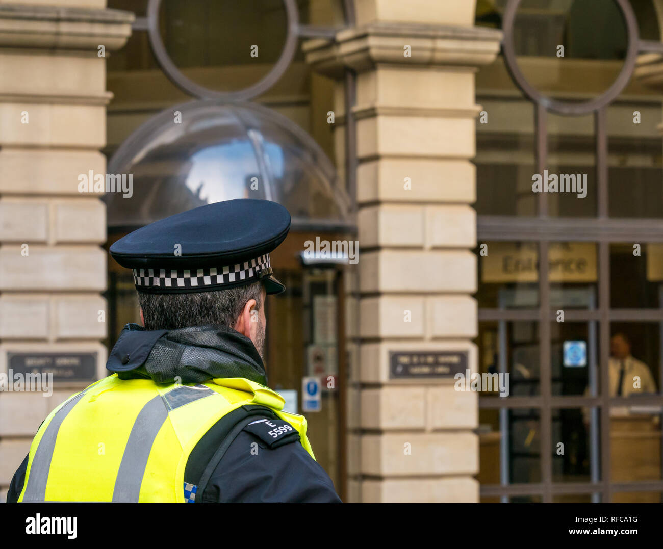 Policeman in yellow vest on duty at Edinburgh Sheriff Court. Edinburgh, Scotland, UK - Stock Image