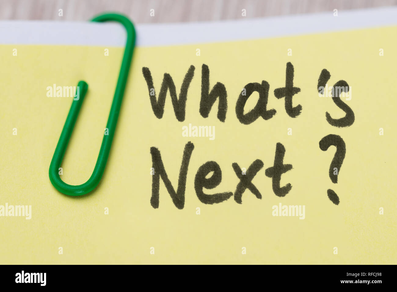 Close-up Of What's Next Text On Yellow Adhesive Notes With Green Paper Clip - Stock Image