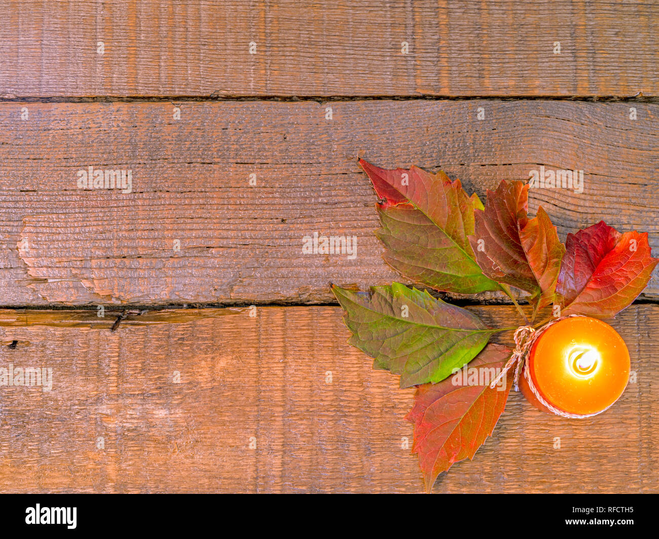 Rustic old barn wood background background with autumn leaves and copy space with a lighted orange candle. - Stock Image