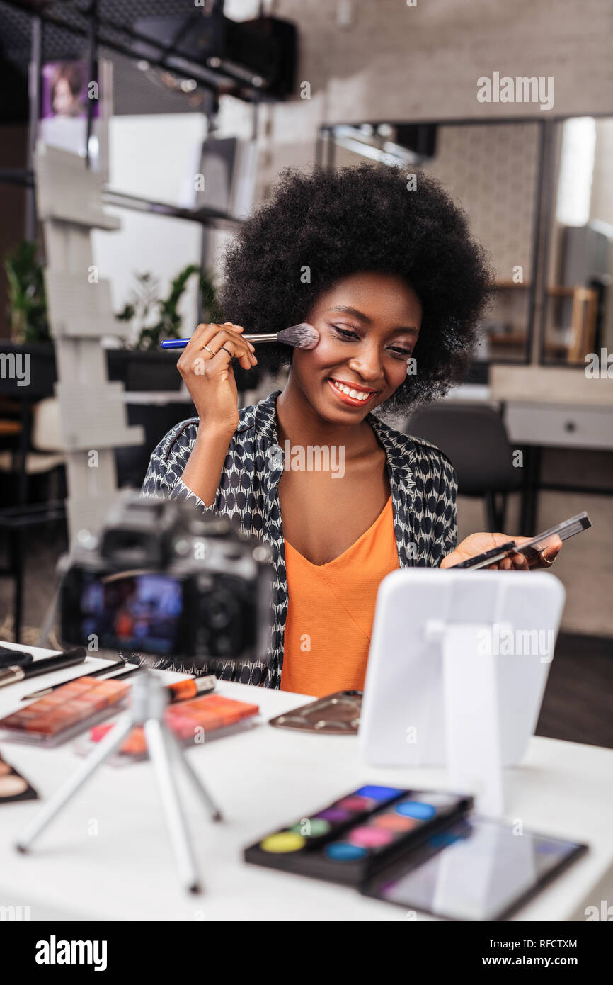 Positive dark-skinned woman with curly hair sitting in front of the mirror - Stock Image