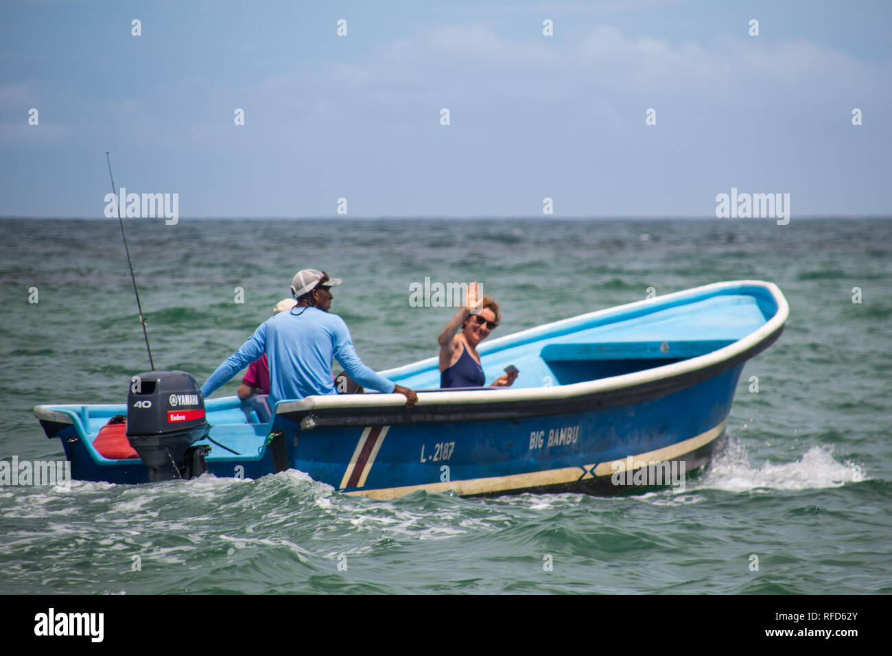 A photo of a boat with two tourists embarking on a dolphin watching trip at Manzanillo, Costa Rica - Stock Image