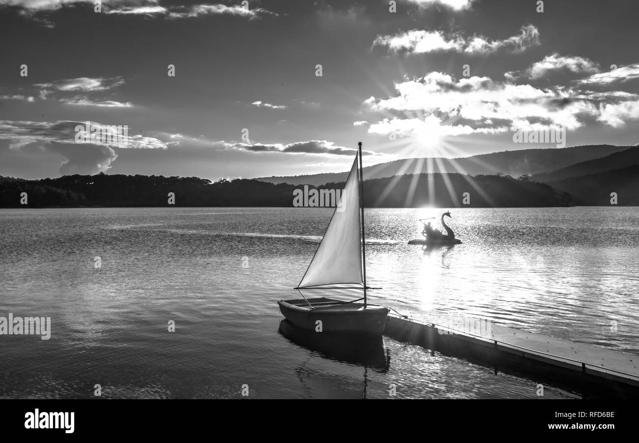 Lonely sailboat in the beautiful sunset with sun stars shines from sky and the surface of the lake is calm and peaceful when watching them Stock Photo