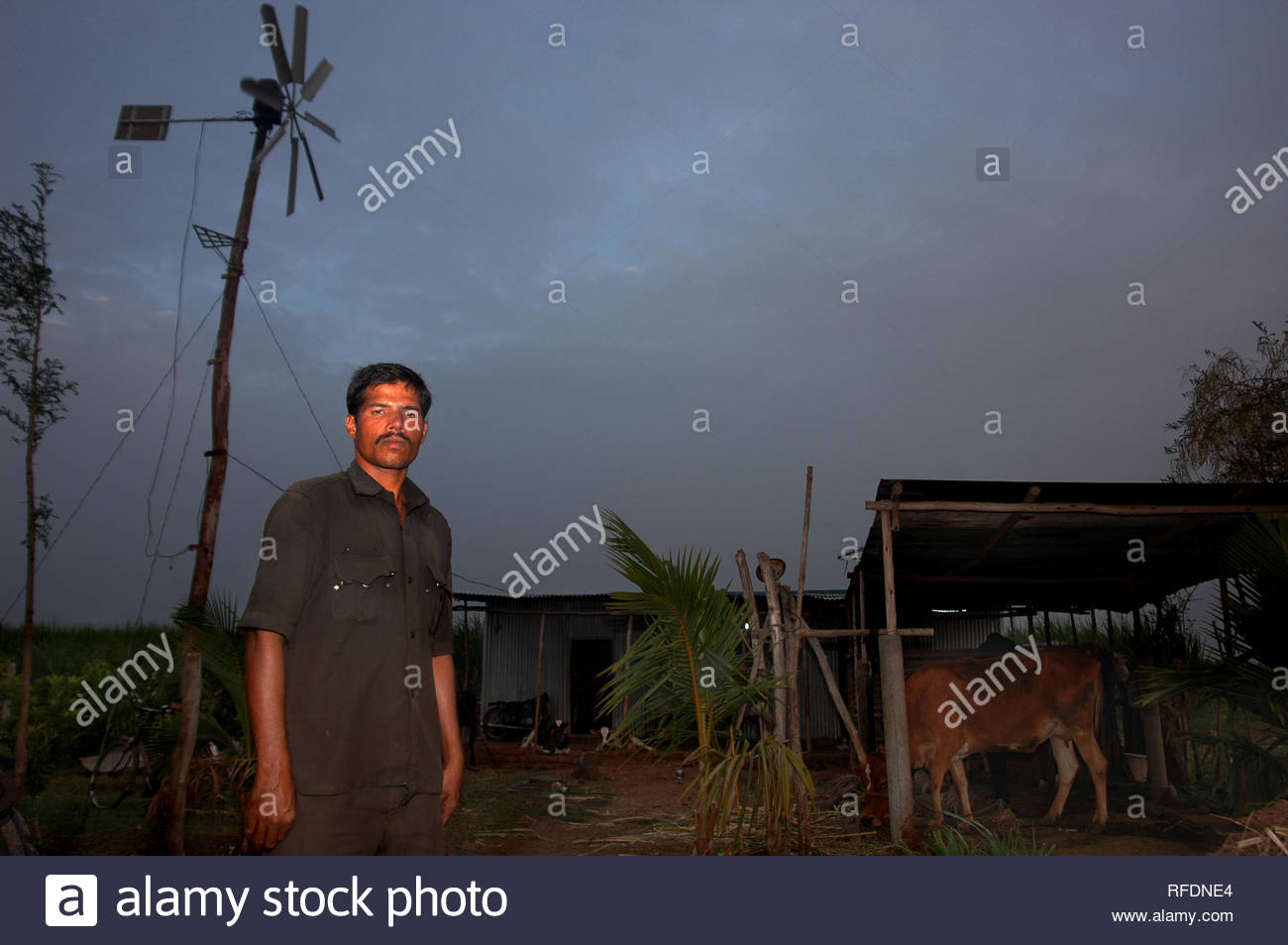 """Automobile mechanic Ashok Awati stands before his indigenously designed windmill, at his village on the outskirts of Sangli, Maharashtra, India on May 8, 2013. At being told by the electricity department that he could get power to his home only if he could pay for erecting electric poles, Ashok Awati went ahead and designed his own windmill to generate power to light up his house consisting of 8 members of his family. Currently he generates electricity enough to run a television set, a DVD player and five bulbs to light up his residence. """"I spent about Rs 20,000 for parts like the gear box, ma - Stock Image"""