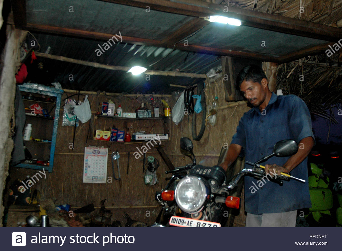 """Automobile mechanic Ashok Awati fixes a motorcycle using light generated by his indigenously designed windmill, in his shanty at a village on the outskirts of Sangli, Maharashtra, India on May 8, 2013. At being told by the electricity department that he could get power to his home only if he could pay for erecting electric poles, Ashok Awati went ahead and designed his own windmill to generate power to light up his house consisting of 8 members of his family. Currently he generates electricity enough to run a television set, a DVD player and five bulbs to light up his residence. """"I spent about - Stock Image"""