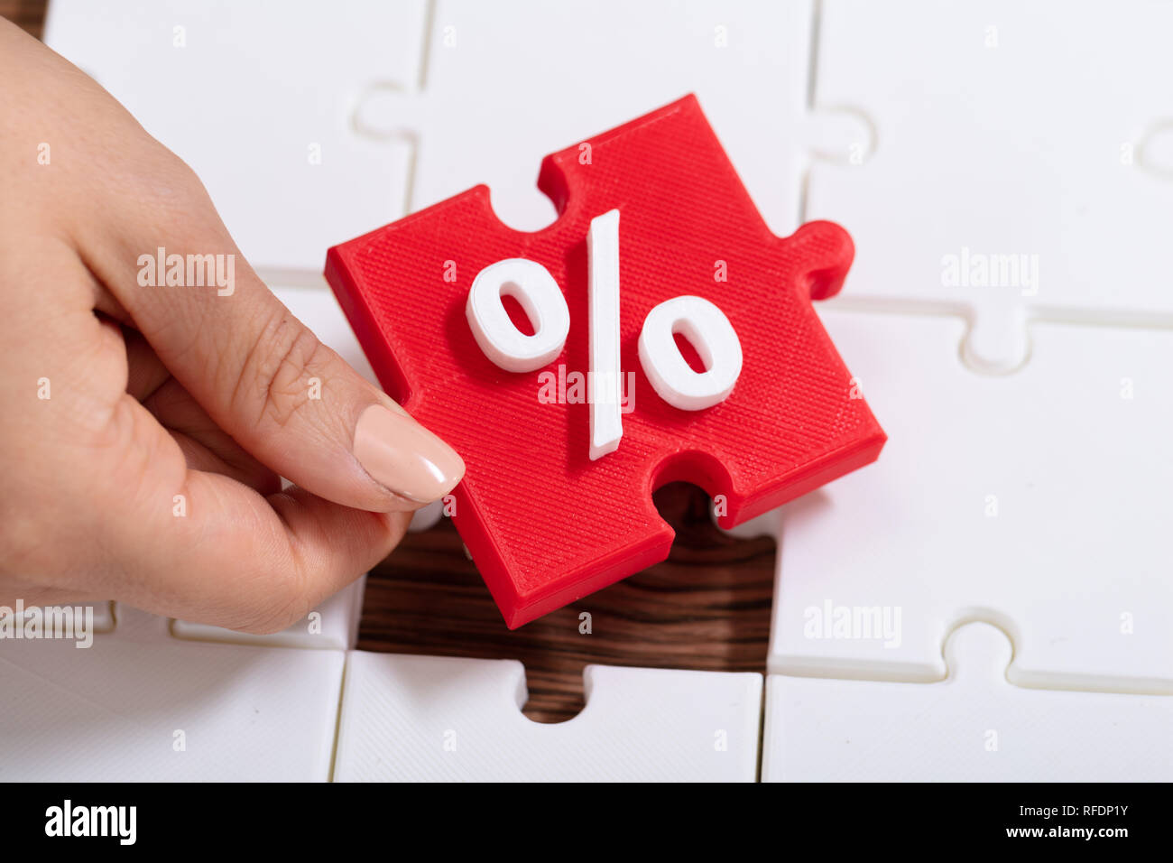 An Overhead View Of Hand Holding Red Jigsaw Puzzle With White Percentage Symbol - Stock Image