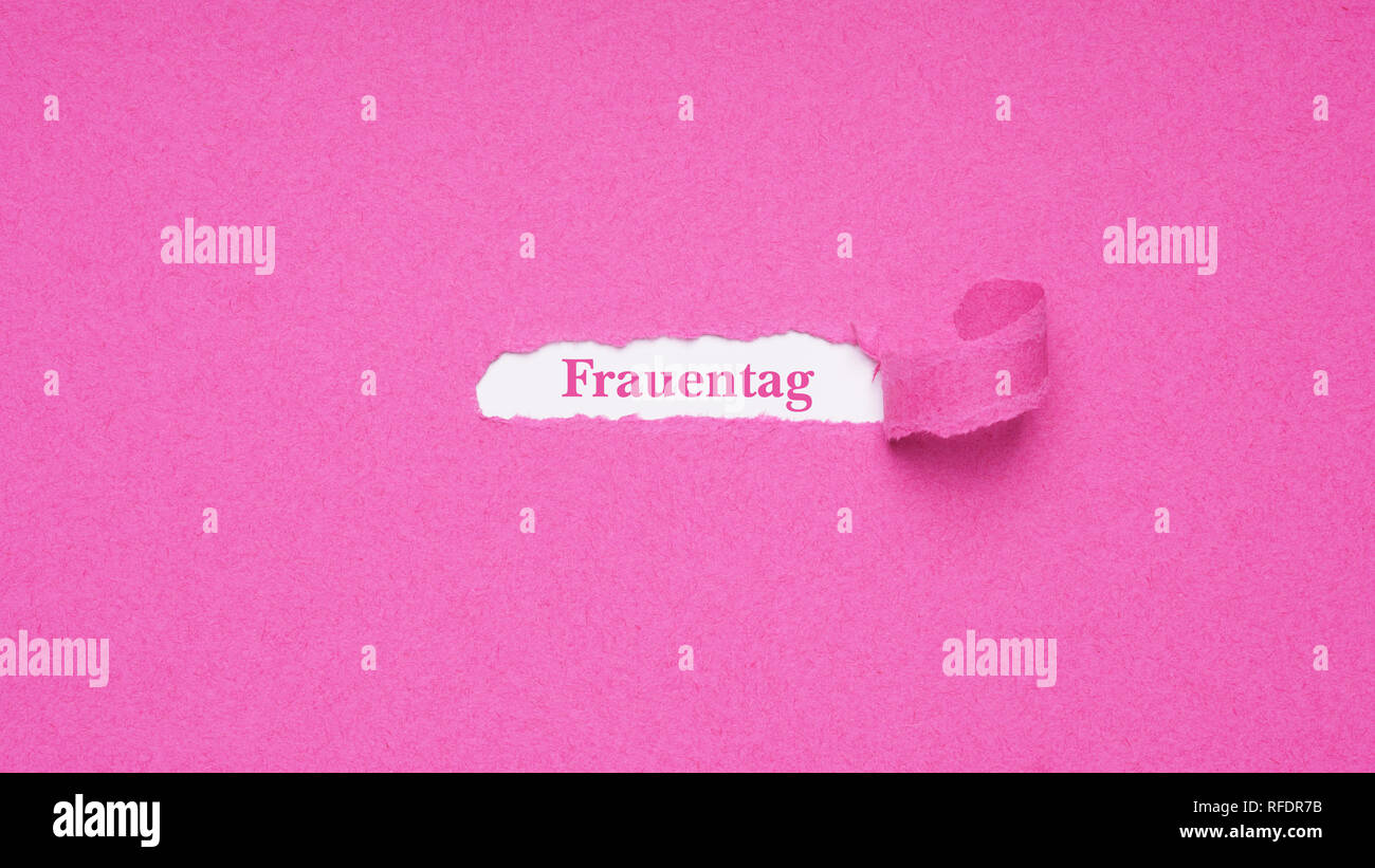 Frauentag is German for Women's Day which is celebrated on March 8 - text revealed by hole torn in pink paper background - Stock Image