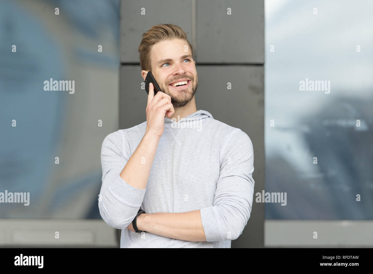 Happy to hear you. Man bearded walks with smartphone, urban background. Man pleasant smiling face speaks on smartphone. Guy pleased answer call on smartphone. Pleasant conversation with friend. - Stock Image