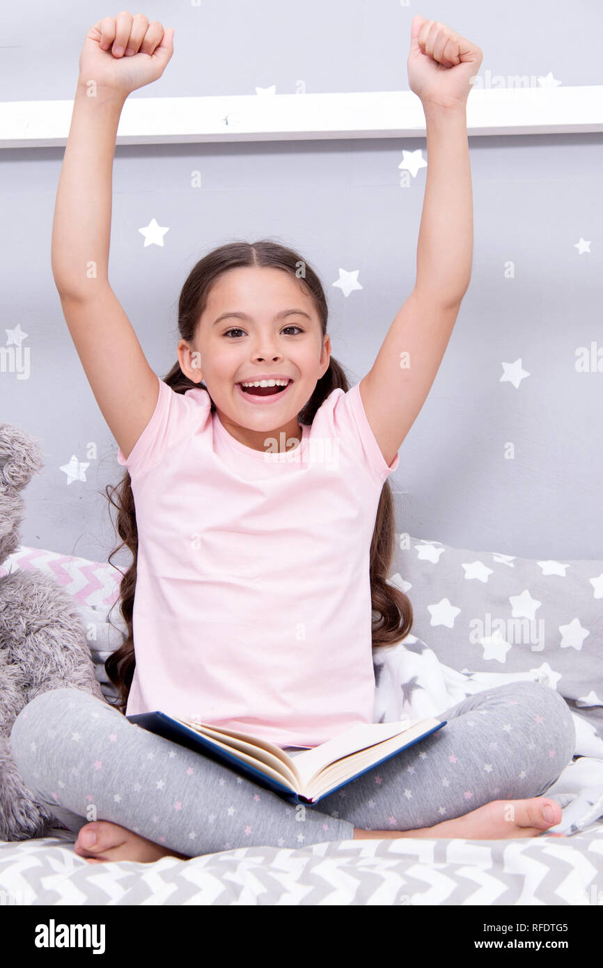 Finished reading book. Girl child sit bed with teddy bear finished reading book. Kid ready to go to bed. Finally finished that book. Girl kid long hair cute pajamas relax and read book to bear toy. Stock Photo