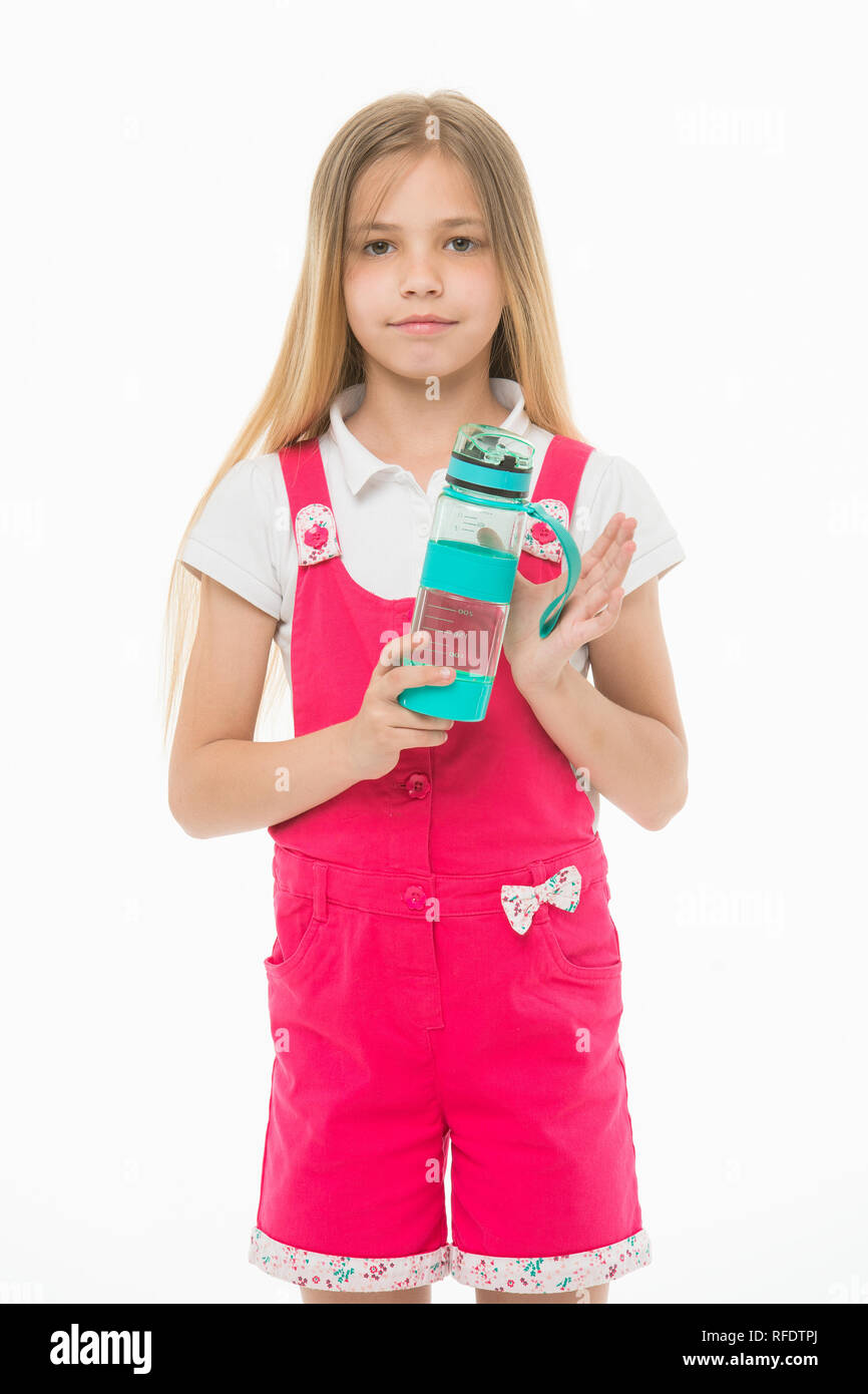 Little girl with plastic bottle isolated on white. Thirsty child in pink jumpsuit hold water bottle. Drinking water for health. Thirst and dehydration. Childhood activity and energy. - Stock Image