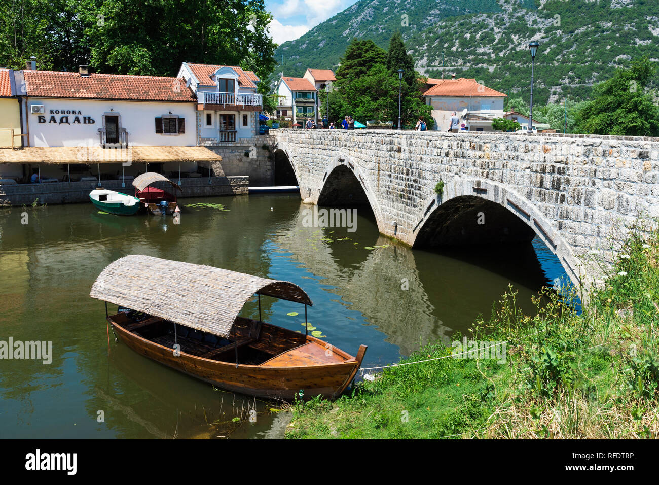 Tourist boat anchored near a Roman bridge, Skadar Lake, Virpazar, Montenegro - Stock Image